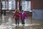 People walk through flood water on a residential street in Doncaster, England, as parts of England endured heavy rain, with some scores of people rescued or forced to evacuate their homes, and travel plans thrown into chaos, Friday Nov. 8, 2019. Torrential rain has drenched parts of north and central England, forcing some to evacuate their homes and stranding a small group of people in a shopping centre overnight. (Danny Lawson/PA via AP)