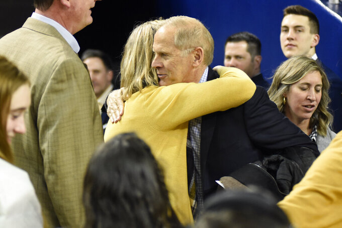 Former Michigan coach John Beilein, right, greets fans before Michigan's NCAA college basketball game against Nebraska, Thursday, March 5, 2020, in Ann Arbor, Mich. (AP Photo/Jose Juarez)