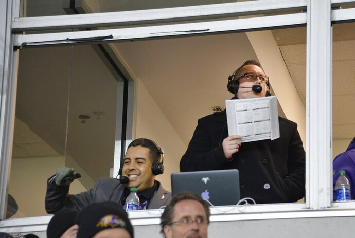 ADDS DATE - This Dec. 15, 2019, photo shows Baltimore Ravens Spanish-speaking broadcast team, play-by-play announcer David Andrade, right, and color commentator Gustavo Salazar, left, can be heard on La Nueva 87.7 FM, in the booth at M&T Bank Stadium. (Kevin Richardson/The Baltimore Sun via AP)
