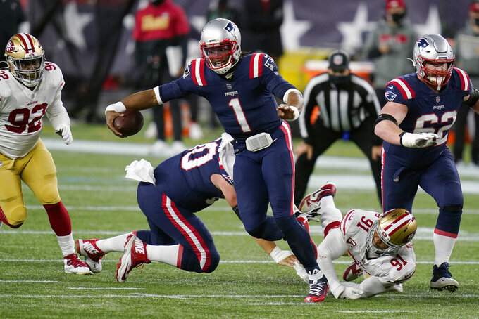 New England Patriots quarterback Cam Newton (1) runs from the grasp of San Francisco 49ers defensive end Arik Armstead (91) in the second half of an NFL football game, Sunday, Oct. 25, 2020, in Foxborough, Mass. (AP Photo/Charles Krupa)