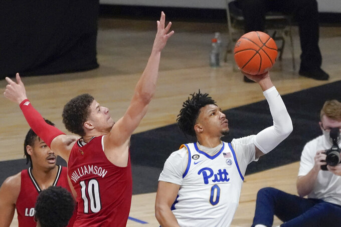 Pittsburgh's Ithiel Horton (0) shoots as Louisville's Samuell Williamson (10) defends during the second half of an NCAA college basketball game Tuesday, Dec. 22, 2020, in Pittsburgh. (AP Photo/Keith Srakocic)