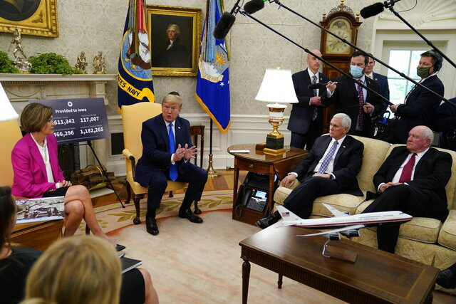 President Donald Trump speaks during a meeting with Gov. Kim Reynolds, R-Iowa, left, in the Oval Office of the White House, Wednesday, May 6, 2020, in Washington. Agriculture Secretary Sonny Perdue, right seated, and Vice President Mike Pence listen.(AP Photo/Evan Vucci)