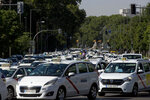 Taxi drivers block a main avenue during a taxi driver protest in downtown Madrid, Spain, Tuesday, June 30, 2020. Taxi drivers are demanding  assistance due to lack of clients and private hire. (AP Photo/Manu Fernandez)