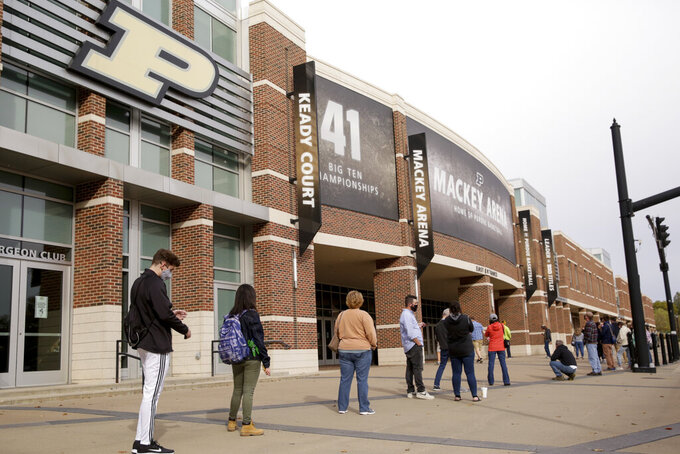 FILE - In this Oct. 14,l 2020, file photo, voters line up outside Purdue University's Mackey Arena for early voting ahead of the 2020 general election, in West Lafayette, Ind. The Tippecanoe County Board of Elections used Mackey Arena as a satellite polling location Wednesday. NFL, NBA, NHL, Major League Baseball, Major League Soccer and college venues are serving various roles in unprecedented ways, including providing space for people to vote while social distancing on Election Day. (Nikos Frazier/Journal & Courier via AP)