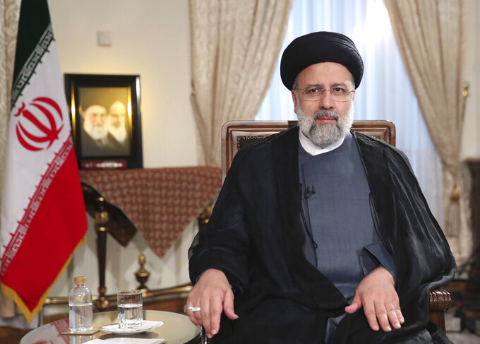 In this photo released by the official website of the office of the Iranian Presidency, President Ebrahim Raisi attends a live televised interview with state-run TV, at the presidency office in Tehran, Iran, Saturday, Sept. 4, 2021. (Iranian Presidency Office via AP)