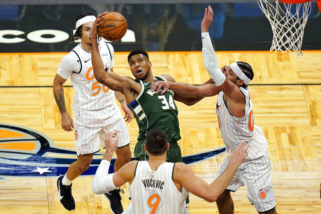 Milwaukee Bucks forward Giannis Antetokounmpo (34) tries to get control of a loose ball between Orlando Magic guard Cole Anthony, bak left, center Nikola Vucevic (9) and forward Aaron Gordon, right, during the second half of an NBA basketball game, Monday, Jan. 11, 2021, in Orlando, Fla. (AP Photo/John Raoux)