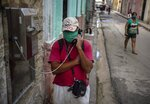 Wearing a protective face mask amid the new coronavirus pandemic, a man speaks on a public phone in Old Havana, Cuba, Monday, Oct. 26, 2020. Few countries in Latin America have seen as dramatic a change in U.S. relations during the Trump administration or have as much at stake in who wins the election. (AP Photo/Ramon Espinosa)