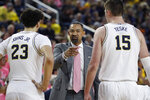Michigan head coach Juwan Howard, center, talks to his team during the first half of an NCAA college basketball game against Wisconsin, Thursday, Feb. 27, 2020, in Ann Arbor, Mich. (AP Photo/Carlos Osorio)