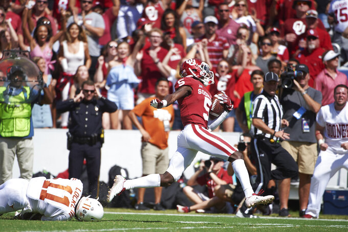 Oklahoma wide receiver Marquise Brown (5) breaks free for a 77-yard touchdown reception against Texas during the second half of an NCAA college football game at the Cotton Bowl, Saturday, Oct. 6, 2018, in Dallas. (AP Photo/Cooper Neill)