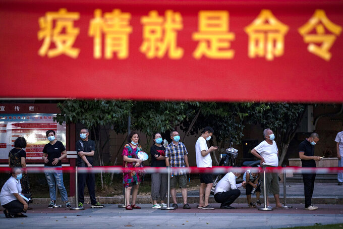 """Residents line up for Covid-19 tests near a banner with the words """"Epidemic is the Order"""" in Wuhan in central China's Hubei province Tuesday, Aug. 3, 2021. China's worst coronavirus outbreak since the start of the pandemic a year and a half ago escalated Wednesday with dozens more cases around the country, the sealing-off of one city and the punishment of its local leaders. (Chinatopix Via AP)"""
