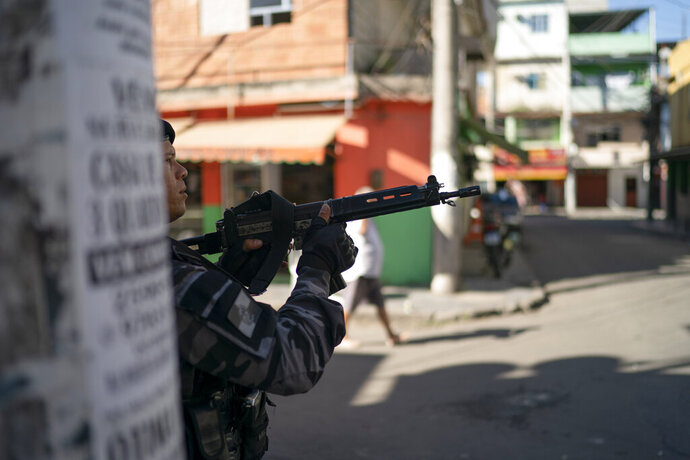 FILE - In this July 31, 2019 file photo, a police officer aims his weapon during an operation in the Mare complex slum of Rio de Janeiro, Brazil. (AP Photo/Leo Correa, File)
