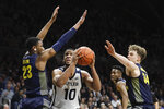 Butler's Bryce Nze (10) shoots against Marquette's Jamal Cain (23) and Jayce Johnson (34) during the first half of an NCAA college basketball game, Friday, Jan. 24, 2020, in Indianapolis. (AP Photo/Darron Cummings)