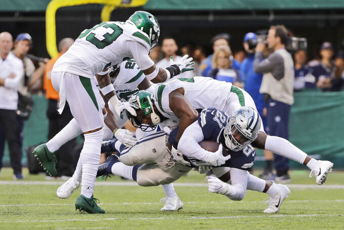 Dallas Cowboys' Ezekiel Elliott, bottom, is tackled by New York Jets defense during the first half of an NFL football game, Sunday, Oct. 13, 2019, in East Rutherford, N.J. (AP Photo/Frank Franklin II)