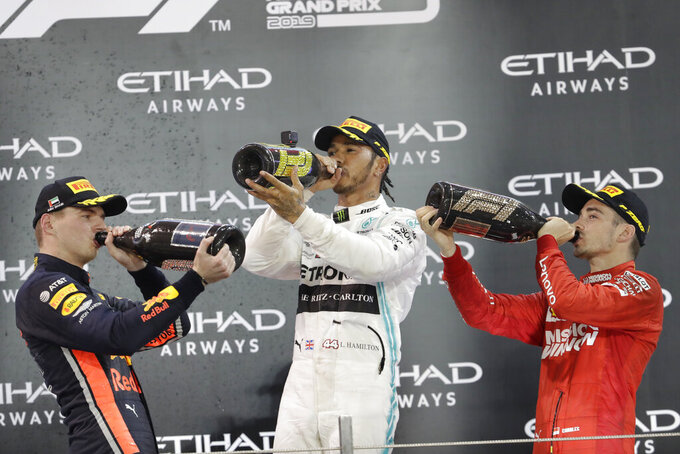 FILE - In this Dec. 1, 2019, file photo, Mercedes driver Lewis Hamilton of Britain , centre, celebrates on the podium after wining the Emirates Formula One Grand Prix as Red Bull driver Max Verstappen of the Netherland's, left, and Ferrari driver Charles Leclerc of Monaco, look on, at the Yas Marina racetrack in Abu Dhabi, United Arab Emirates. Four months after the opening race was called off amid last-minute pandemonium the Formula One season finally gets underway this weekend in Austria.(AP Photo/Luca Bruno, File)