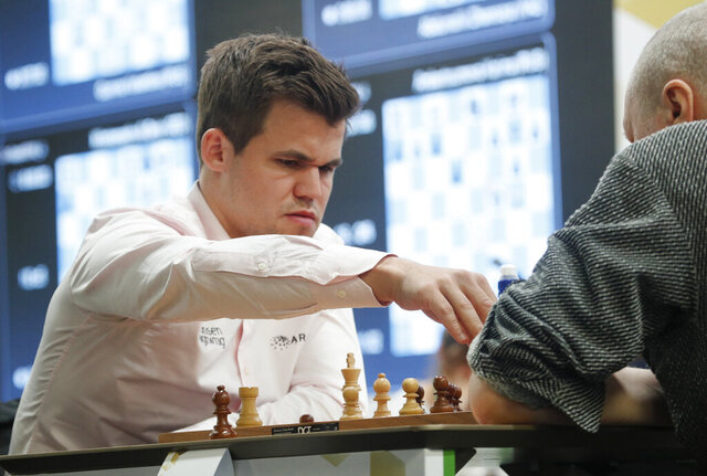 FILE - In this file photo dated Wednesday, Dec. 26, 2018, Chess World Champion Magnus Carlsen, left, from Norway during a game against Russia's Nikolai Vlassov during the World Rapid and Blitz Chess Championships in St. Petersburg, Russia. Carlsen is a No. 1 player in chess and is moving to the top of the standings in Fantasy Premier League soccer, according to his Twitter page Monday Dec. 16, 2019. (AP Photo/Dmitri Lovetsky, FILE)