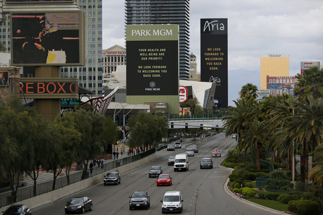 FILE - The Park MGM and Aria hotel-casinos flash messages on their closing due to the coronavirus, in Las Vegas in this March 16, 2020 file photo. Casino giant MGM Resorts International said Tuesday, Sept. 29, 2020, it's teaming with a firm that provided COVID-19 screenings to the National Hockey League playoffs and a health care provider to high-volume events in an optional conference attendee safety plan at its U.S. hotels and casinos. (AP Photo/John Locher, File)