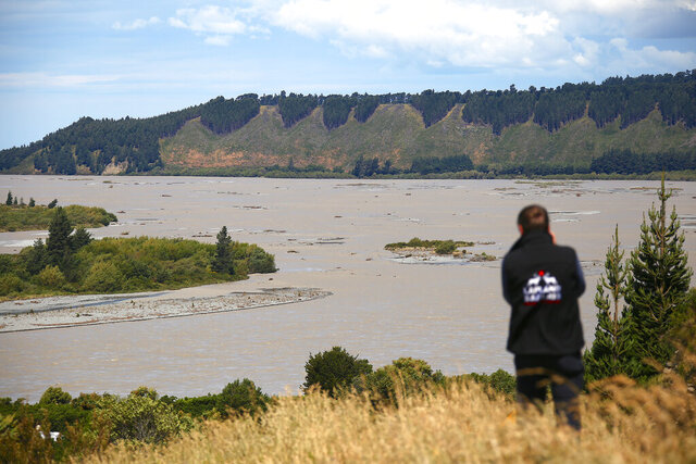 In this Sunday, Dec. 8, 2019, photo, a tourist photographs the rising water in the Rakaia Gorge 85kms (50 miles) west of Christchurch in Canterbury, New Zealand as stormy weather across New Zealand over the weekend caused disruptions and road closures in many parts of the country. Nearly 1,000 tourists are stranded in the small New Zealand town of Franz Josef after stormy weekend weather triggered landslides and flooding along the town's main highway. (David B Gray via AP)