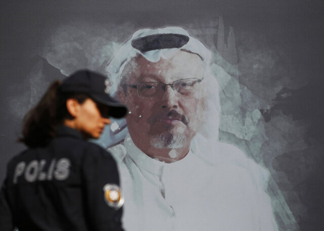 FILE - In this Wednesday, Oct. 2, 2019 file photo, a Turkish police officer walks past a picture of slain Saudi journalist Jamal Khashoggi prior to a ceremony, near the Saudi Arabia consulate in Istanbul, marking the one-year anniversary of his death. On Wednesday, March 25, 2020, Turkish prosecutors have formally charged two former aides of Saudi Crown Prince Mohammed bin Salman and 18 other Saudi nationals over the 2018 killing of Khashoggi. All suspects however, have left Turkey and Saudi Arabia has rejected Turkish calls for their return to face trial in Turkey. (AP Photo/Lefteris Pitarakis, File)