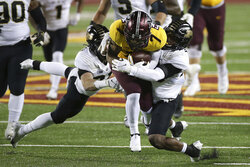 Minnesota wide receiver Chris Autman-Bell is tackled by Purdue safety Brennan Thieneman, left, and linebacker Jaylan Alexander during the first half of an NCAA college football game Friday, Nov. 20, 2020, in Minneapolis. (AP Photo/Stacy Bengs)