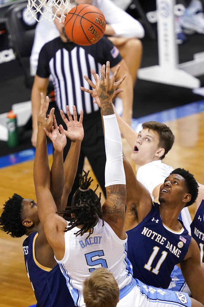 North Carolina forward Armando Bacot (5) battles Notre Dame guard Tony Sanders Jr., left, and Notre Dame forward Juwan Durham (11) during the second half of an NCAA college basketball game in the second round of the Atlantic Coast Conference tournament in Greensboro, N.C., Wednesday, March 10, 2021. (AP Photo/Gerry Broome)