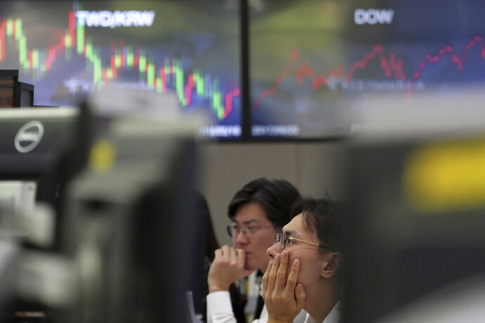 Currency traders watch monitors at the foreign exchange dealing room of the KEB Hana Bank headquarters in Seoul, South Korea, Tuesday, Sept. 17, 2019. Shares were mostly lower in Asia on Tuesday after an attack on Saudi Arabia's biggest oil processing plant caused crude prices to soar, prompting selling of airlines and other fuel-dependent industries. (AP Photo/Ahn Young-joon)