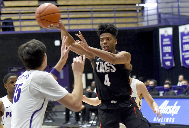 Gonzaga guard Aaron Cook, right, passes the ball past Portland forward Hayden Curtiss, left, during the second half of an NCAA college basketball game in Portland, Ore., Saturday, Jan. 9, 2021. (AP Photo/Steve Dykes)