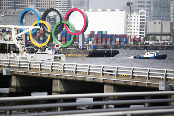 "Tugboats move a symbol installed for the Olympic and Paralympic Games Tokyo 2020 on a barge from its usual spot off the Odaiba Marine Park in Tokyo Thursday, Aug. 6, 2020. The five Olympic rings floating on a barge in Tokyo Bay were removed on Thursday for what is being called ""maintenance,"" and officials says they will return to greet next year's Games. The Tokyo Olympics have been postponed for a year because of the coronavirus pandemic and are to open on July 23, 2021. The Paralympics follow on Aug. 24. (AP Photo/Hiro Komae)"