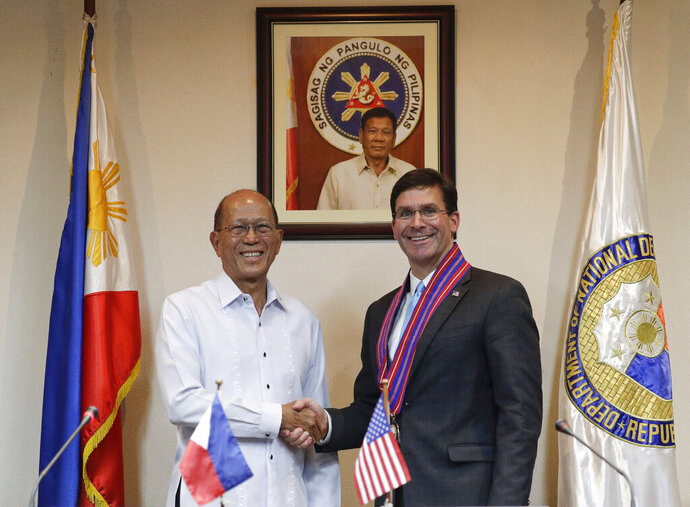 U.S. Defense Secretary Mark Esper, right, shakes hands with his Philippine counterpart Delfin Lorenzana after a press conference at the Philippine Department of National Defense in Quezon city, metropolitan Manila, Philippines Tuesday, Nov. 19, 2019. Esper met with his Philippine counterpart to advance the alliance as well as strengthen regional security cooperation to uphold international rules and norms. (AP Photo/Aaron Favila)