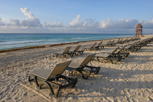 FILE - In this June 11, 2020 file photo, lounge chairs fill an empty beach in Cancun, Mexico. In a bill approved unanimously Tuesday, Sept. 30, 2020, Mexico's Senate has voted to levy fines of up to $47,000 against hotels, restaurants or other property owners who restrict access to the country's beaches. (AP Photo/Victor Ruiz, File)