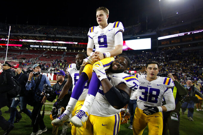 FILE - In this Nov. 10, 2019, file photo, LSU quarterback Joe Burrow (9) is carried by LSU nose tackle Tyler Shelvin (72) after an NCAA football game against Alabama, in Tuscaloosa, Ala. LSU quarterback Joe Burrow is The Associated Press college football player of the year in a landslide vote.  Burrow, who has led the top-ranked Tigers to an unbeaten season and their first College Football Playoff appearance, received 50 of 53 first-place votes from AP Top 25 poll voters and a total of 156 points. (AP Photo/John Bazemore, File)