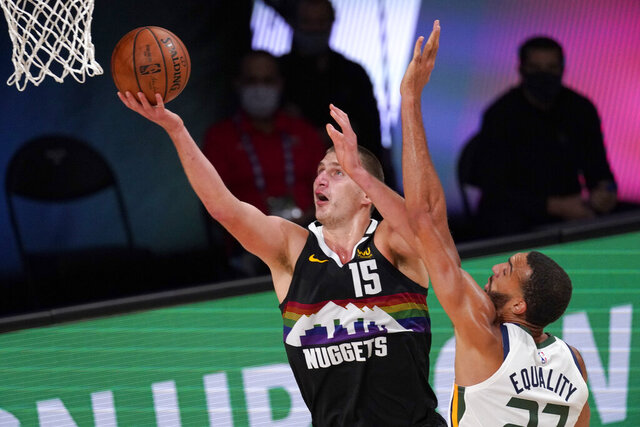 Denver Nuggets' Nikola Jokic (15) goes up for a shot as Utah Jazz's Rudy Gobert (27) defends during the second half an NBA first round playoff basketball game, Tuesday, Sept. 1,2020, in Lake Buena Vista, Fla. (AP Photo/Mark J. Terrill)