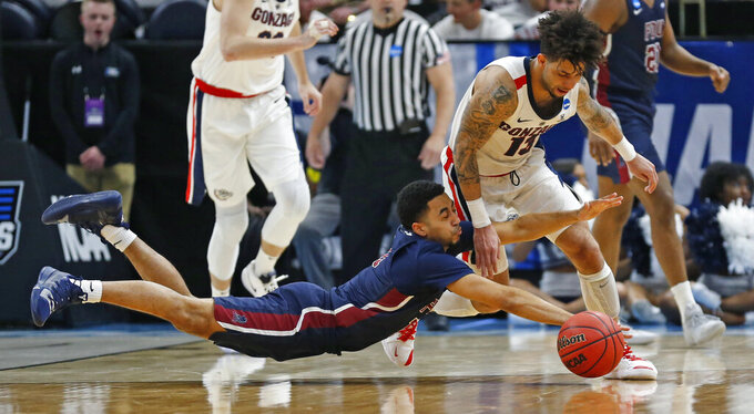 Gonzaga guard Josh Perkins, right, battles Fairleigh Dickinson guard Tyler Jones, bottom, for a loose ball during the second half of a first-round game in the NCAA men's college basketball tournament Thursday, March 21, 2019, in Salt Lake City. (AP Photo/Rick Bowmer)