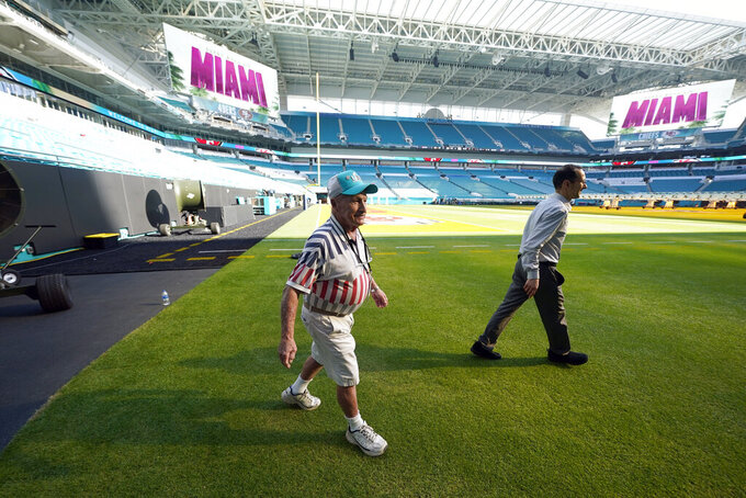 Super Bowl Groundskeeper George Toma, left, walks along the sideline of Hard Rock Stadium Tuesday, Jan. 28, 2020, in Miami Gardens, Fla., in preparation for the NFL Super Bowl 54 football game. (AP Photo/David J. Phillip)