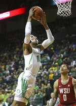Oregon's Kenny Wooten, left, goes up for a shot against Washington State's Isaiah Wade during the first half of an NCAA college basketball game Sunday, Jan 27, 2019, in Eugene, Ore. (AP Photo/Chris Pietsch)