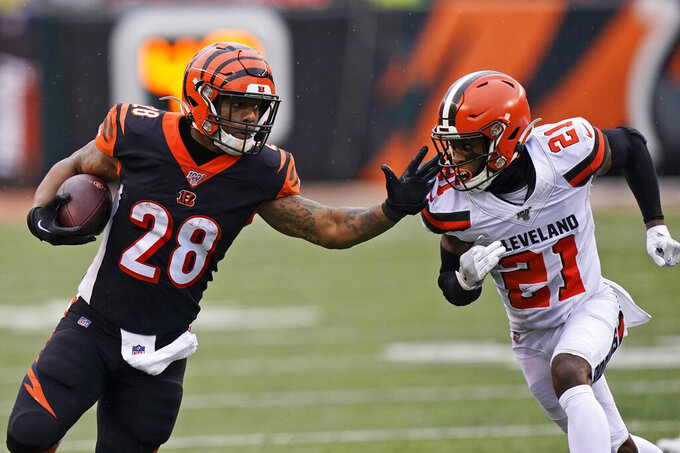 Cincinnati Bengals running back Joe Mixon (28) rushes against Cleveland Browns cornerback Denzel Ward (21) during the first half of an NFL football game, Sunday, Dec. 29, 2019, in Cincinnati. (AP Photo/Bryan Woolston)