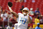 Los Angeles Chargers quarterback Justin Herbert (10) throws during pregame warmups prior to the start of an NFL football game against the Washington Football Team, Sunday, Sept. 12, 2021, in Landover, Md. (AP Photo/Alex Brandon)