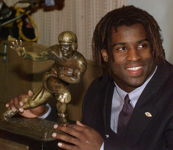 FILE - In this Dec. 12, 1998, file photo, Texas tailback Ricky Williams poses with the Heisman trophy at the Downtown Athletic Club in New York. Brian Hobbs remembers getting a call in 2014 to let him know retired football star Ricky Williams was interested in selling his Heisman Trophy. Hobbs is now selling the trophy as part of his collection of Williams memorabilia being offered by Heritage Auctions' Fall Sports Memorabilia Collectibles offerings. (AP Photo/Suzanne Plunkett, File)