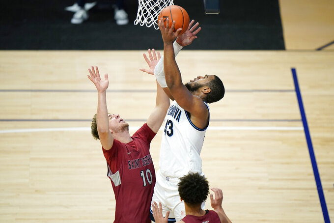 Villanova's Eric Dixon, right, goes up for a shot against Saint Joseph's Anton Jansson during the second half of an NCAA college basketball game, Saturday, Dec. 19, 2020, in Villanova, Pa. (AP Photo/Matt Slocum)