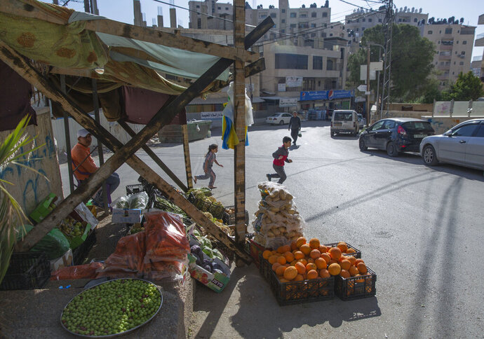In this Tuesday, April 28, 2020 photo, a Palestinian vendor displays his vegetables in the street as the main vegetable market remains closed, part of lockdown and quarantine measures to protect residents from the coronavirus, in the West Bank village of Kufr Aqab. As the coronavirus pandemic gathered strength in April, community leaders in Kufr Aqab, a Palestinian neighborhood on the outskirts of Jerusalem, tried to impose lockdown and quarantine measures to protect residents. The problem: There are no police. Kufr Aqab is within city boundaries drawn up by Israel, but it's on the opposite side of Israel's separation barrier. That means neither the Israeli police nor Palestinian security forces are able to operate there. (AP Photo/Nasser Nasser)