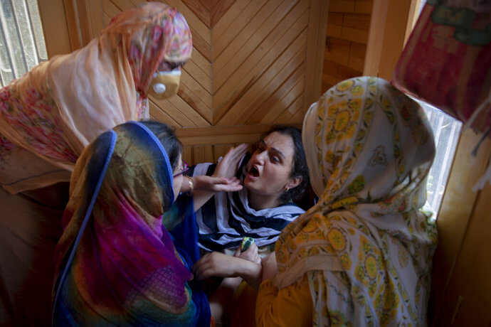 Relatives comfort the grieving daughter of civilian Bashir Ahmed Khan at their residence on the outskirts of Srinagar, Indian controlled Kashmir, Wednesday, July 1, 2020. Suspected rebels attacked paramilitary soldiers in the Indian portion of Kashmir, killing Khan and a paramilitary soldier, according to government sources. The family refutes the claim. (AP Photo/ Dar Yasin)