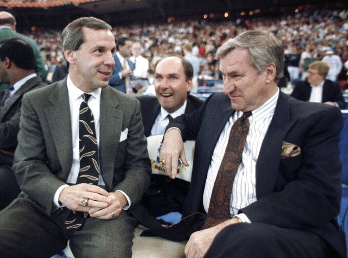 FILE - In this March 30, 1991, file photo, then-Kansas coach Roy Williams, left, and North Carolina coach Dean Smith talk before the start of the first NCAA national semifinal game in Indianapolis. North Carolina announced Thursday, April 1, 2021, that Hall of Fame basketball coach Roy Williams is retiring after a 33-year career that includes three national championships.  (AP Photo/Bob Jordan, File)