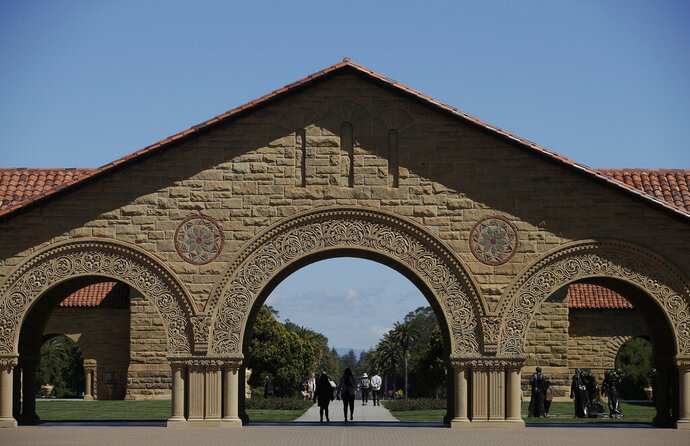 FILE - In this April 9, 2019 file photo, pedestrians walk on the campus at Stanford University in Stanford, Calif. Authorities are investigating the on-campus death of a Stanford University undergraduate student but do not suspect foul play. Deputies responded Friday, Jan. 17, 2020 to a medical emergency at a residence. The Stanford Daily reported that it was the Theta Delta Chi fraternity house. The man, who was not identified, died at the scene. (AP Photo/Jeff Chiu, File)