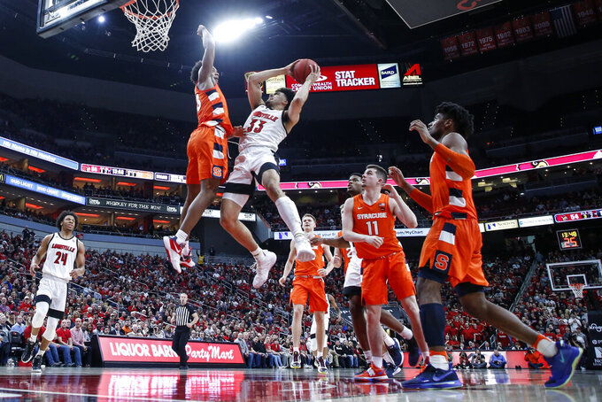 Louisville forward Jordan Nwora (33) shoots as he's defended by Syracuse forward Elijah Hughes (33) during the second half of an NCAA college basketball game Wednesday, Feb. 19, 2020, in Louisville, Ky. Louisville won 90-66. (AP Photo/Wade Payne)