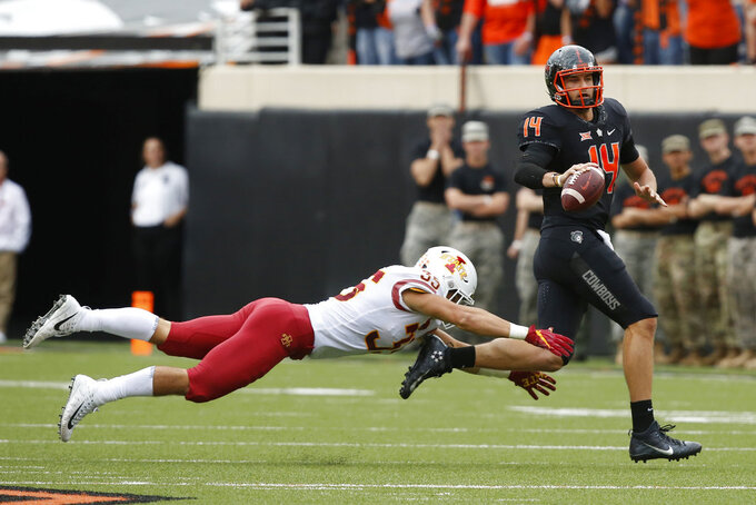 Oklahoma State quarterback Taylor Cornelius (14) is chased by Iowa State linebacker Jake Hummel (35) int he second half of an NCAA college football game in Stillwater, Okla., Saturday, Oct. 6, 2018. (AP Photo/Sue Ogrocki)