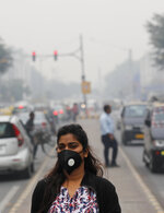 A commuter walks wearing a pollution mask amidst thick layer of smog in New Delhi, India, Thursday, Nov. 14, 2019. Schools in India's capital have been shut for Thursday and Friday after air quality plunged to a severe category for the third consecutive day, enveloping New Delhi in a thick gray haze of noxious air. (AP Photo/Manish Swarup)