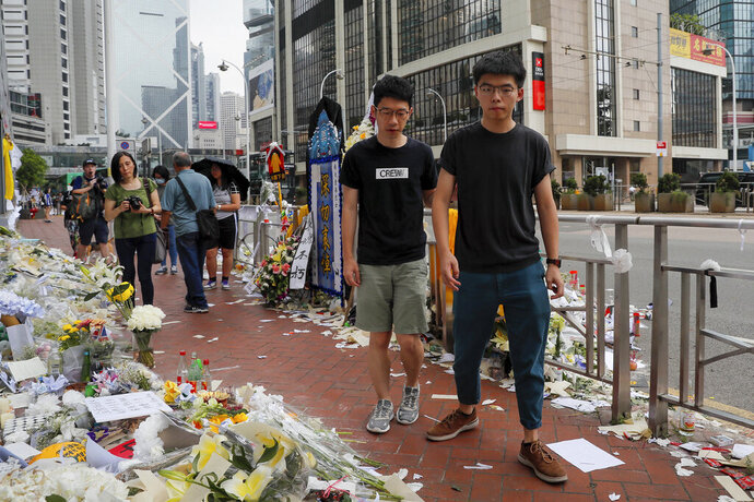 Pro-democracy activist Joshua Wong, right, is accompanied by Nathan Law as they pay respect to a protester who fell to his death after hanging a protest banner against an extradition bill in Hong Kong, Monday, June 17, 2019. Wong, a leading figure in Hong Kong's 2014 Umbrella Movement demonstrations, was released from prison on Monday and vowed to soon join the latest round of protests. (AP Photo/Kin Cheung)