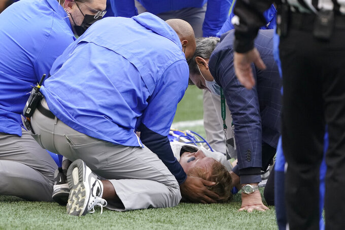Los Angeles Rams quarterback John Wolford is tended to by medical personnel after being injured during the first half of an NFL wild-card playoff football game against the Seattle Seahawks, Saturday, Jan. 9, 2021, in Seattle. (AP Photo/Ted S. Warren)