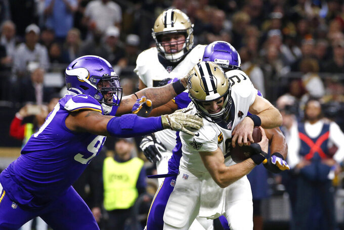Minnesota Vikings defensive end Danielle Hunter tries to tackle New Orleans Saints quarterback Drew Brees (9) in the first half of an NFL wild-card playoff football game, Sunday, Jan. 5, 2020, in New Orleans. (AP Photo/Butch Dill)