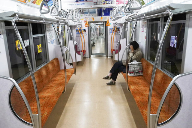 A woman rides an empty subway Thursday, May 21, 2020, in Tokyo. Tokyo is still under a coronavirus state of emergency until the end of May though there have been no hard lockdowns. (AP Photo/Eugene Hoshiko)