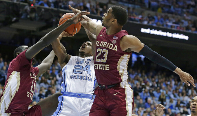 North Carolina's Kenny Williams (24) shoots while Florida State's Christ Koumadje and M.J. Walker (23) defend during the first half of an NCAA college basketball game in Chapel Hill, N.C., Saturday, Feb. 23, 2019. (AP Photo/Gerry Broome)